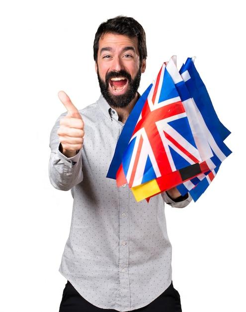 Uomo bello con la barba che tiene molte bandiere e con il pollice in su Foto Gratuite