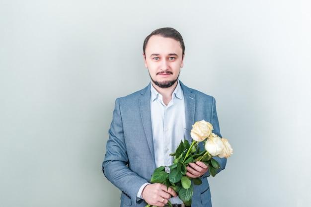 Uomo bello con la barba in piedi su uno sfondo grigio con un mazzo di rose bianche Foto Premium
