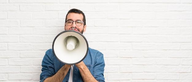 Uomo bello con la barba sopra il muro di mattoni bianco che grida tramite un megafono Foto Premium