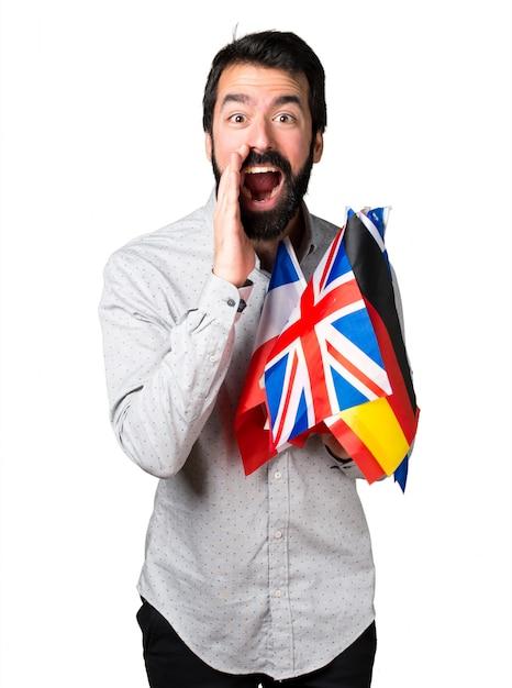Uomo bello con la barba tenendo molte bandiere e gridando Foto Gratuite