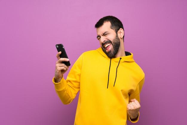 Uomo bello con la felpa gialla con il telefono nella posizione di vittoria Foto Premium
