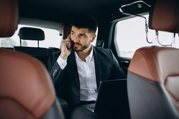 Uomo bello di affari che lavora ad un computer in automobile Foto Gratuite