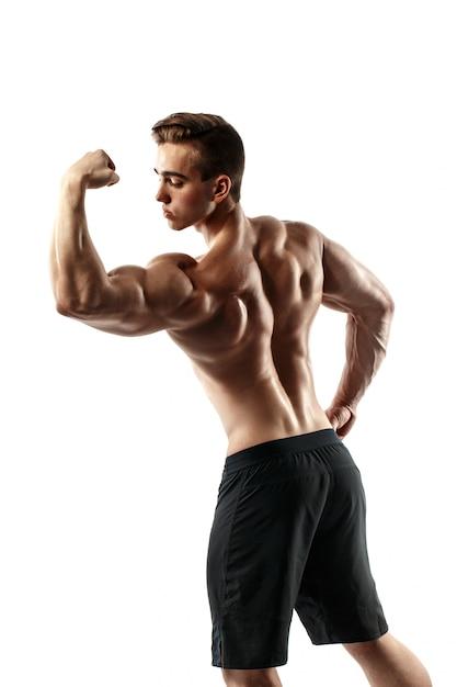 Uomo bello di altissimo livello muscolare che posa sul fondo bianco Foto Premium