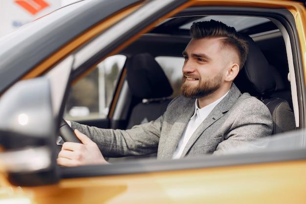Uomo bello ed elegante in un salone di auto Foto Gratuite