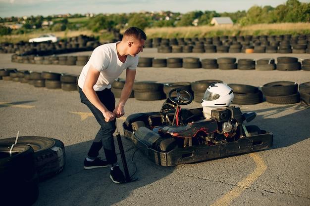 Uomo bello in un karting con un'auto Foto Gratuite