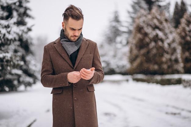 Uomo bello parlare al telefono in un parco di inverno Foto Gratuite
