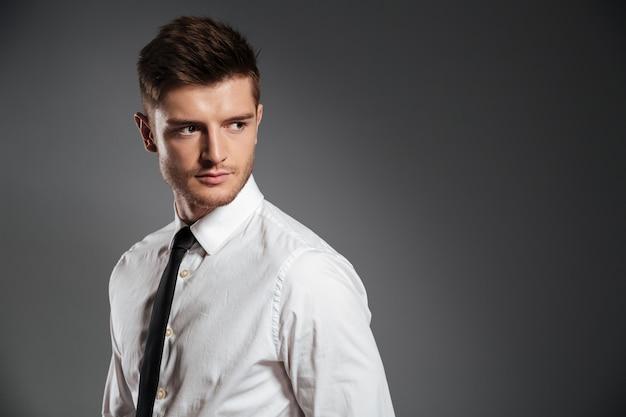 Uomo bello serio in camicia e cravatta in piedi Foto Gratuite