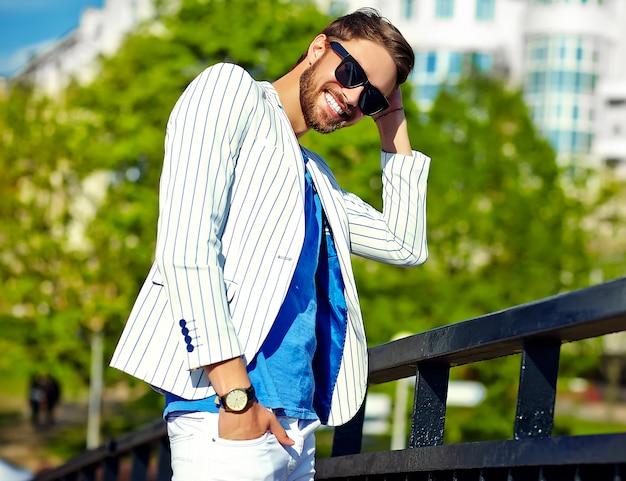 Uomo bello sorridente divertente dei pantaloni a vita bassa in vestito bianco di estate alla moda che posa in via in occhiali da sole Foto Gratuite