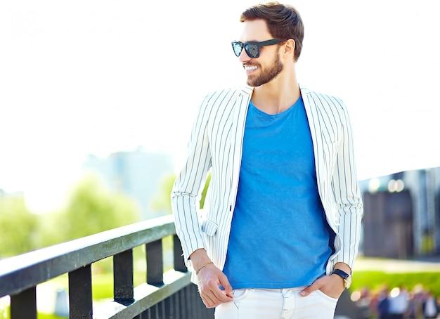 Uomo bello sorridente divertente dei pantaloni a vita bassa in vestito bianco di estate alla moda che posa sul muro di strada in occhiali da sole Foto Gratuite