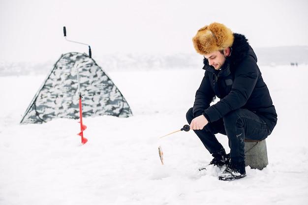 Uomo bello su una pesca invernale Foto Gratuite