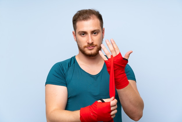 Uomo biondo di sport sopra la parete blu in fasciature di pugilato Foto Premium