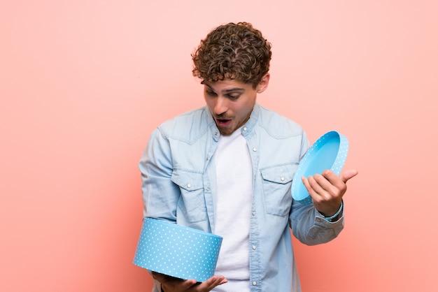 Uomo biondo sopra la parete rosa che tiene un regalo in mano Foto Premium