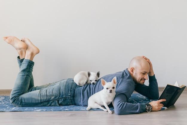 Uomo calvo adulto in abbigliamento alla moda che si trova sulla stuoia di yoga. libro di lettura di un giovane ragazzo. due cuccioli maschii bianchi della chihuahua a casa Foto Premium
