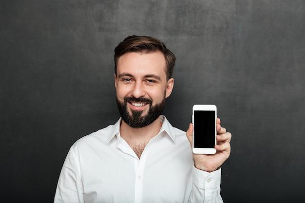 Uomo caucasico del brunette che mostra smartphone sulla dimostrazione della macchina fotografica o che fa pubblicità all'aggeggio sopra lo spazio della copia della grafite Foto Gratuite