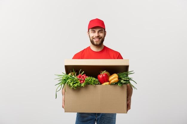 Uomo caucasico del corriere di consegna della drogheria in uniforme rossa con la scatola di drogheria con frutta fresca Foto Premium