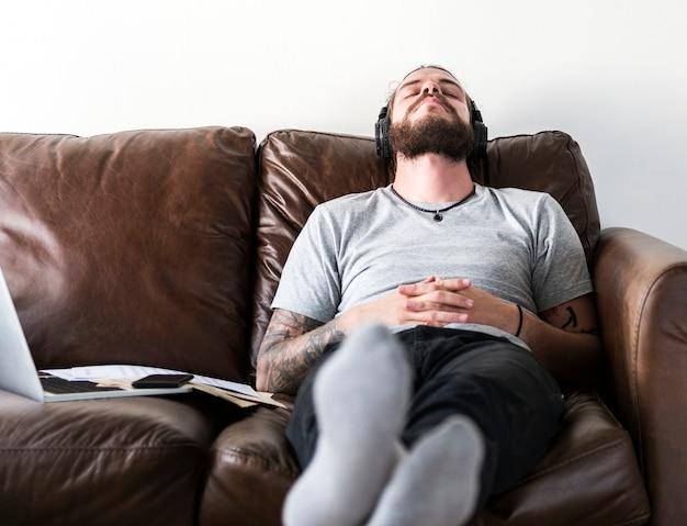 Uomo caucasico prendendo una pausa dal lavoro ascoltando musica Foto Gratuite