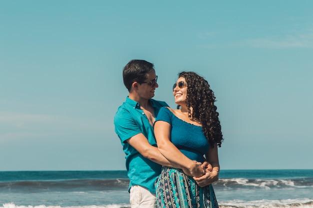 Uomo che abbraccia donna sorridente sulla spiaggia Foto Gratuite