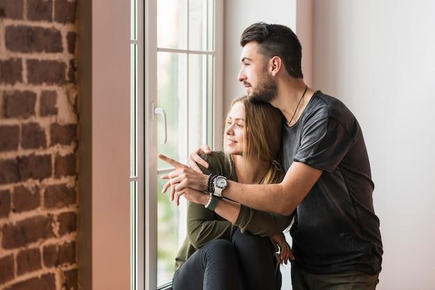 Uomo che abbraccia la sua ragazza che punta a qualcosa vicino alla finestra Foto Gratuite