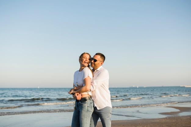 Uomo che abbraccia la sua ragazza da dietro in piedi vicino al mare contro il cielo blu in spiaggia Foto Gratuite
