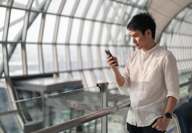 Uomo che aspetta il volo e l'utilizzo di smart phone in aeroporto Foto Premium