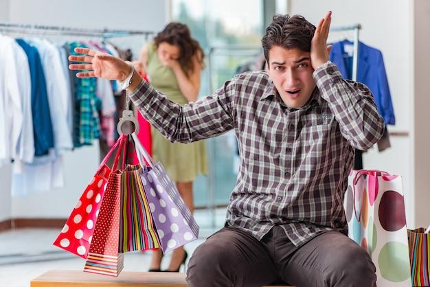 Uomo che aspetta la moglie durante lo shopping natalizio Foto Premium
