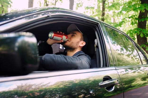 Uomo che beve birra mentre si guida l'auto Foto Premium