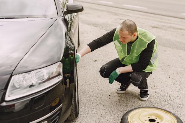 Uomo che cambia ruota rotta sull'automobile Foto Gratuite