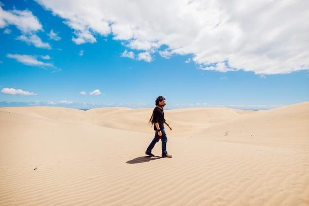 Uomo che cammina su un paesaggio di dune del deserto. uomo che fa un giro turistico tra le dune in una calda giornata estiva. Foto Premium