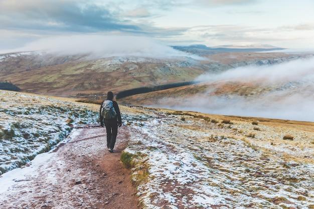 Uomo che cammina sulle colline innevate in inverno Foto Premium