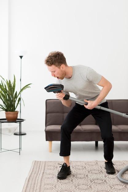 Uomo che canta al vuoto durante la pulizia Foto Gratuite