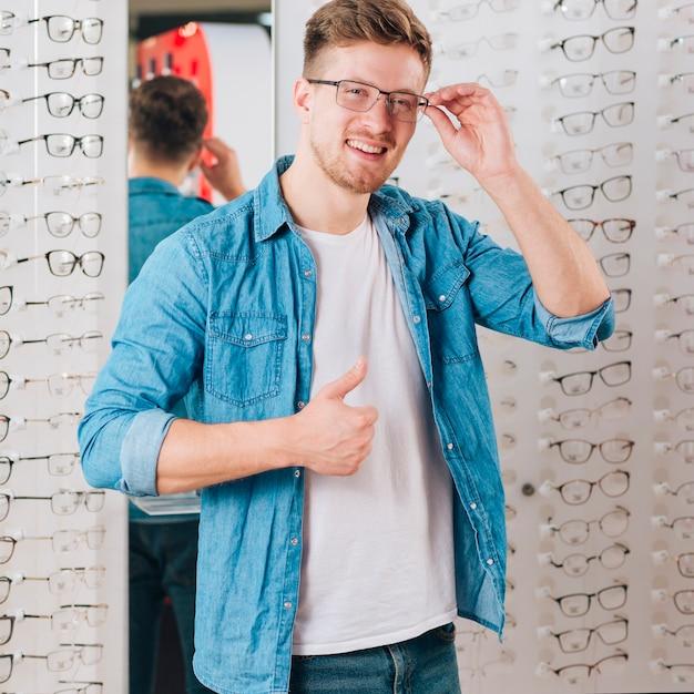 Uomo che cerca nuovi occhiali all'optometrista Foto Gratuite