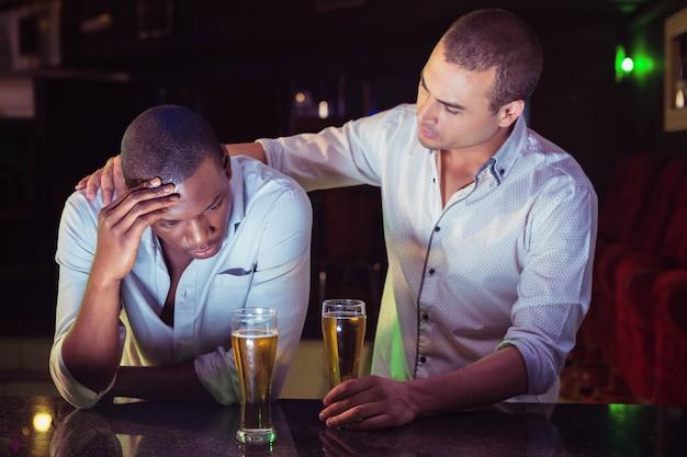 Uomo che conforta il suo amico depresso nel bar Foto Premium