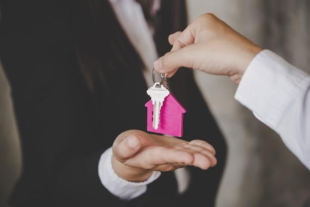 Uomo che consegna le chiavi di casa a una nuova casa all'interno della stanza vuota di colore grigio. Foto Premium