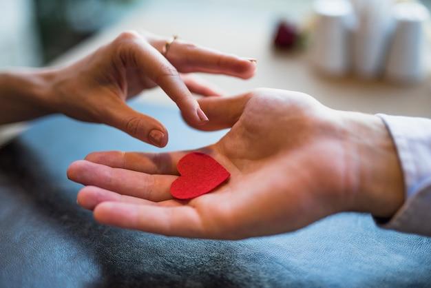 Uomo che dà il cuore rosso dell'ornamento alla donna Foto Gratuite