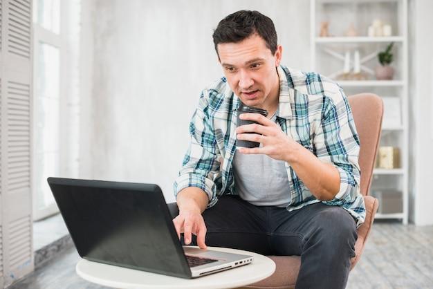 Uomo che digita sul computer portatile e che tiene tazza della bevanda sulla sedia Foto Gratuite