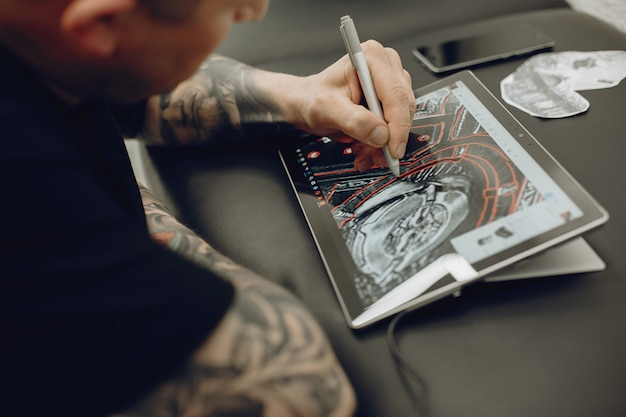 Uomo che disegna lo schizzo in una compressa Foto Gratuite