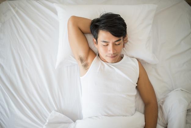 Uomo che dorme sul letto al mattino Foto Gratuite