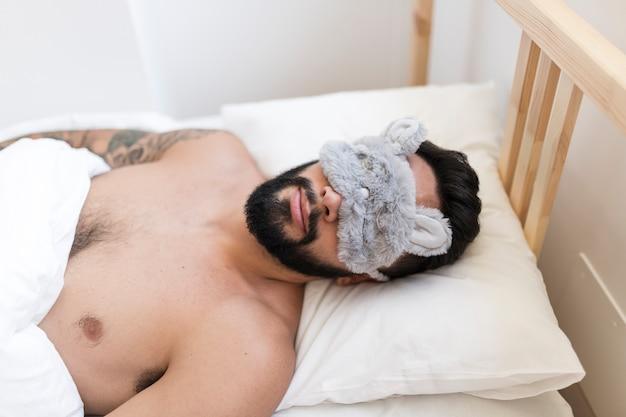 Uomo che dorme sul letto con la maschera del sonno Foto Gratuite