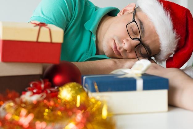 Uomo che dorme sul tavolo con regali di natale e palline Foto Gratuite