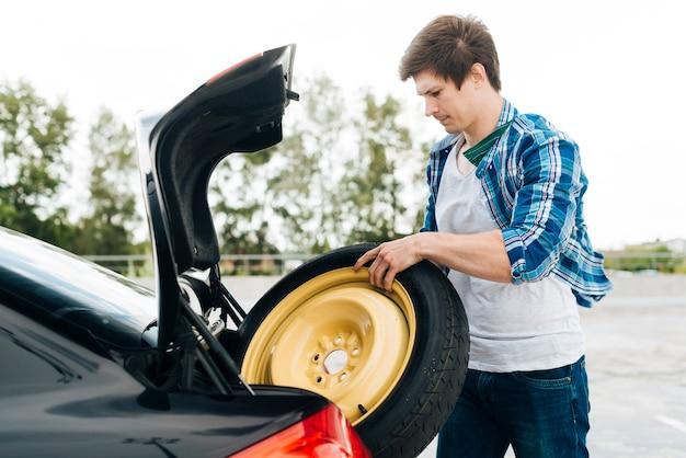 Uomo che elimina la ruota di scorta Foto Gratuite