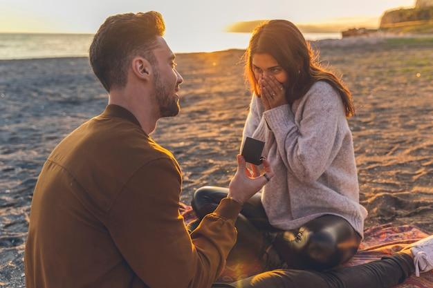 Uomo che fa proposta alla donna sulla riva del mare di sabbia Foto Gratuite