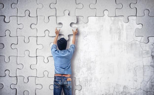 Uomo che fa un puzzle sul muro. muro vuoto con spazio per il testo Foto Premium
