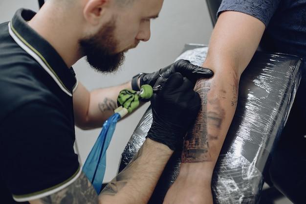 Uomo che fa un tatuaggio in un salone di tatuaggi Foto Gratuite