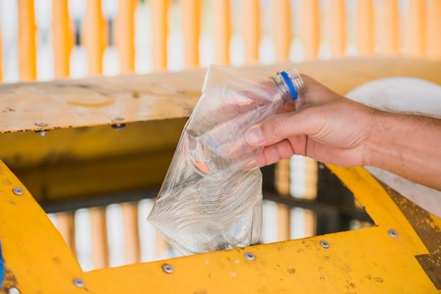 Uomo che getta la bottiglia di plastica nel cestino Foto Gratuite
