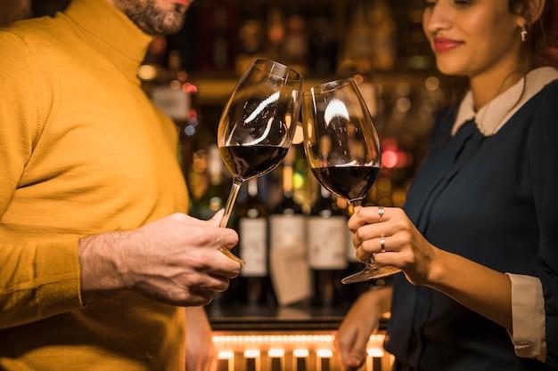 Uomo che gracchiava bicchieri di vino con donna Foto Gratuite