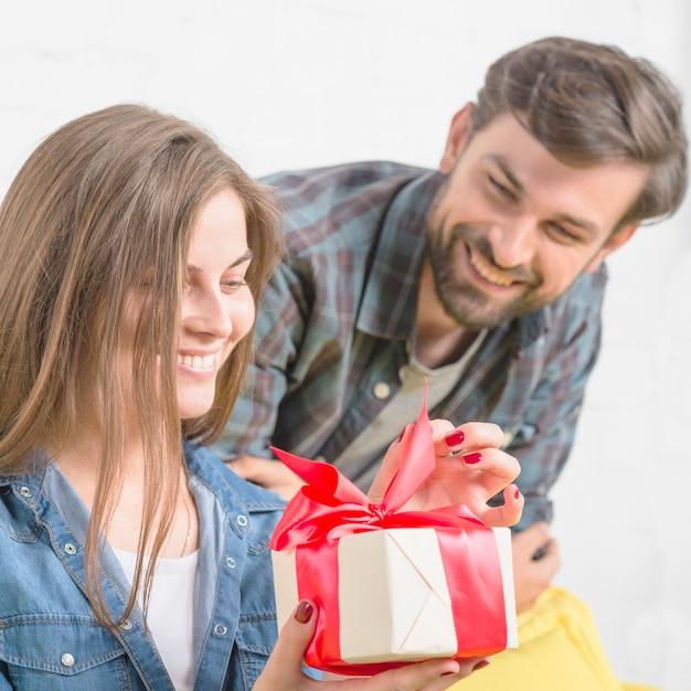 Uomo che guarda la sua ragazza scartare regalo di san valentino Foto Gratuite
