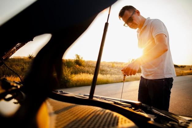 Uomo che guarda le condizioni dell'auto Foto Gratuite