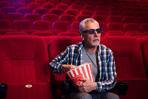 Uomo che guarda un film al cinema Foto Gratuite