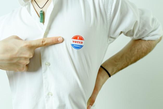 Uomo che indica un adesivo i votato oggi sul petto. Foto Premium