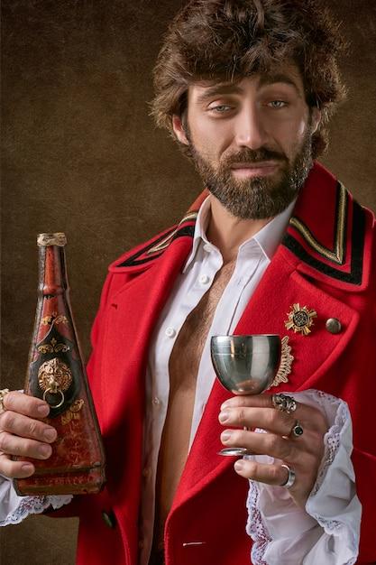 Uomo che indossa cappotto rosso e nero in piedi e in possesso di bottiglia e bicchiere di vino Foto Gratuite
